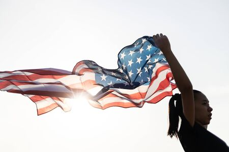 A Young asian woman holding American flag with sun flare. Banco de Imagens