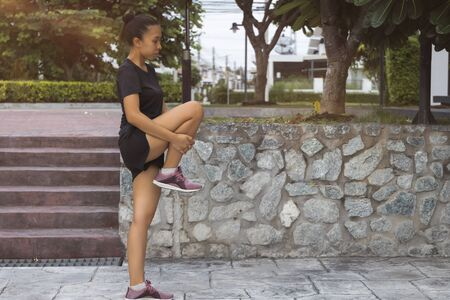 The Young female workout before fitness training session at the park. Healthy young woman warming up outdoors.