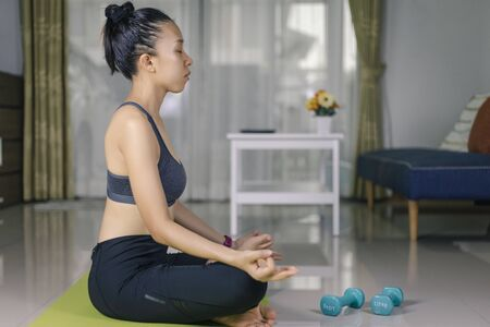 International Day of Yoga concept Asian woman doing meditation for yoga athlete sitting on an exercise mat at home.