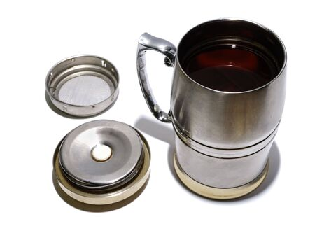 bolter: Cup of tea, tea-strainer and cover on white background