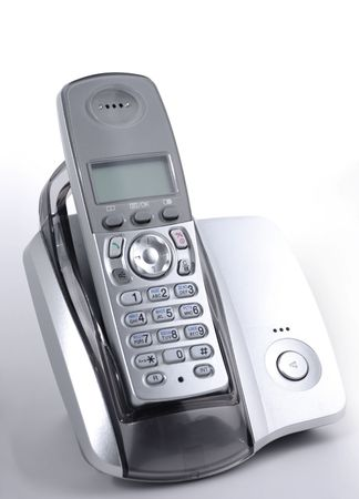 Modern wireless  DECT phone in cradle over gray background Stock Photo