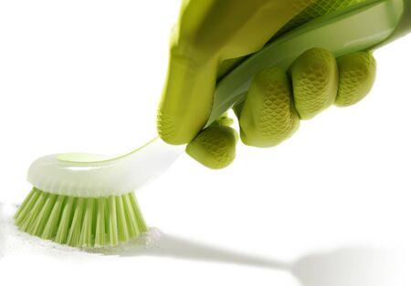 housekeeping: Mano enguantada con un cepillo de lavar en polvo a m�s de fondo blanco