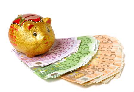 Piggy bank over spray of bills on white background