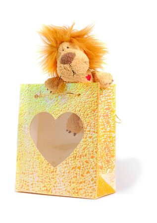 Little stuffed lion with small gift bag over white background