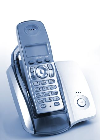 Modern wireless  DECT phone in cradle over blue background photo