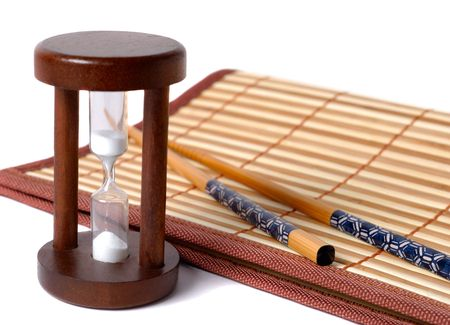 Composition of chopsticks, sand glass and bamboo table-cloth over white background photo