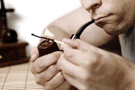 A man lighting a smoking pipe