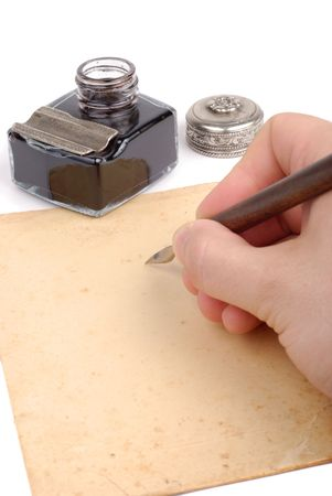 Male hand with quill writing something on old paper photo