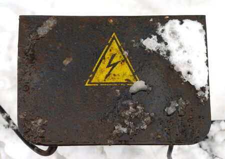 Old rusty power battery over snow background    photo