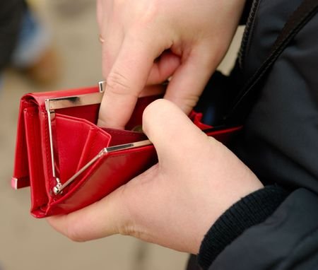 Male hands with red wallet. Outdoor shot.