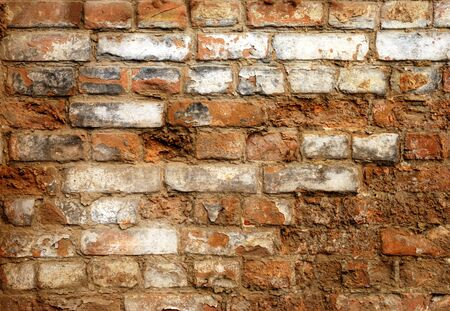 Fragment of old brick wall with gray stucco photo