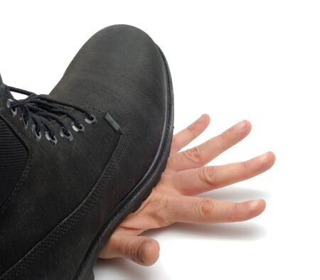 Black boot stepped on man hand isolated with clipping path on white background