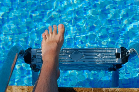 Male bare foot step into pool with blue clean water Stock Photo