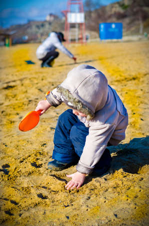 little boy digs in sand on a beach a shovel with mum Stock Photo - 12306296