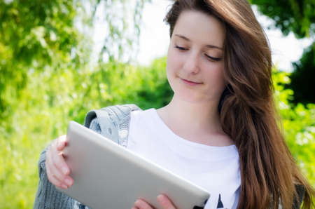 attractive casual young girl working on a touch screen tablet in the park