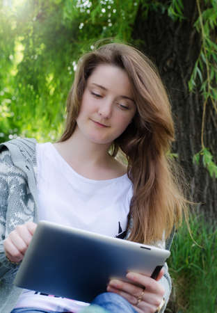 Low angle view of an attractive casual young girl working on a touch screen tablet in the park