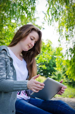 electronic devices: Girl sitting outdoors on a paved driveway in a verdant garden using a touchscreen tablet
