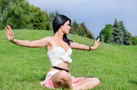 Beautiful woman meditates on green lawn with katana sword  put on feet photo