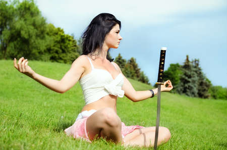 Beautiful woman meditates on green lawn with katana sword stuck into the ground next to her photo