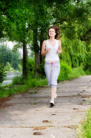 approaching: Girl  jogging along a path through a park as she takes her daily exercise to keep fit