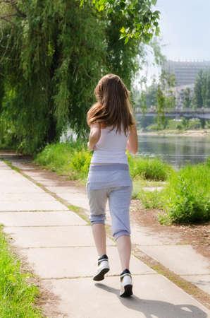 Jonge vrouw joggen weg van de camera langs een pad loopt langs een rivier in een gezondheids-en fitness concept
