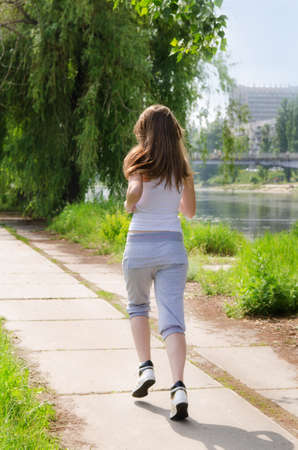 Young woman jogging away from the camera along a pathway running alongside a river in a health and fitness concept
