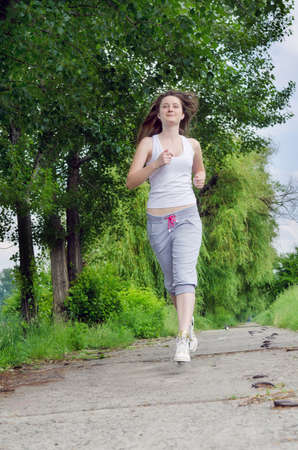 approaching: Young woman in casual clothes jogging along a path through a park as she takes her daily exercise to keep fit