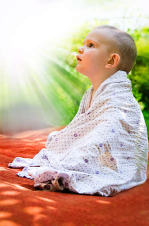 enraptured: Young child sitting draped in a blanket on an orange mat in the garden looking up in awe and wonderment at the rays of the sun