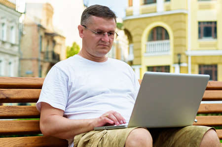 Middle-aged man in glasses sitting on a wooden bench in an urban environment working on his laptop photo