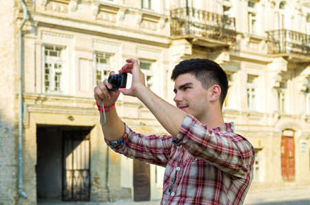 Young man standing taking photographs with a compact camera outside an old historical building Stock Photo - 14615063