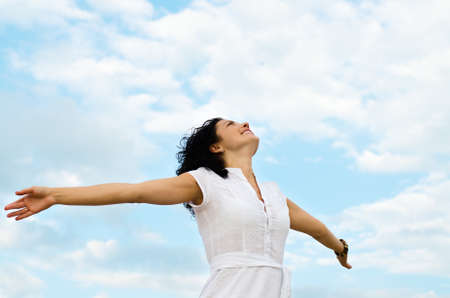 Happy smiling woman standing with outspread arms and her face lifted to the cloudy blue sky Archivio Fotografico