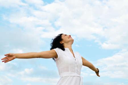 Happy lachende vrouw die zich met gespreide armen en haar gezicht opgeheven naar de helder blauwe hemel Stockfoto