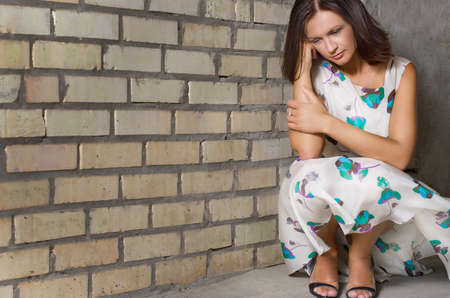 Closeup with copyspace of an unhappy depressed woman crouching down against a brick wall with her head resting on her fist