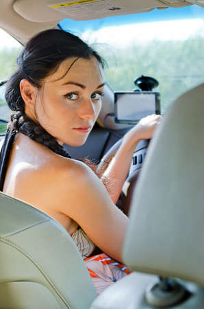 Woman driver seated in the drivers seat looking back into the rear of the car and getting distracted from the road Stock Photo - 14615107