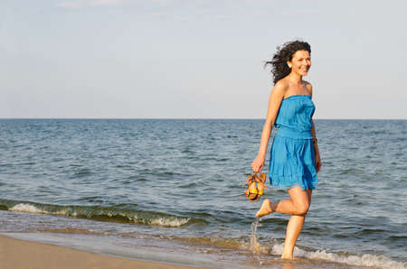Pretty woman running along the edge of the surf on a sandy beach with her shoes in her hand photo
