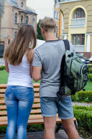 identifying: Rear view of a young couple with a backpack looking at map as they sightsee on their summer vacation
