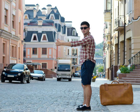 roadside stand: Young man with a large suitcase thumbing a ride in an urban street with historic buildings as he hitchhikes his way around the country