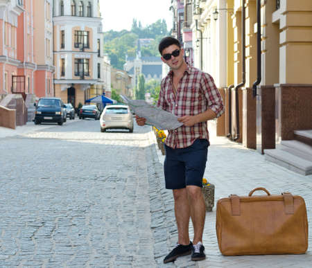 newcomer: Male tourist standing on the sidewalk of an urban street with a suitcase and map trying tofind directions Stock Photo