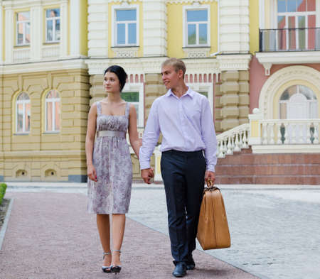 Elegant young couple on vacation walking hand in hand along a sidewalk in an affluent urban environment photo