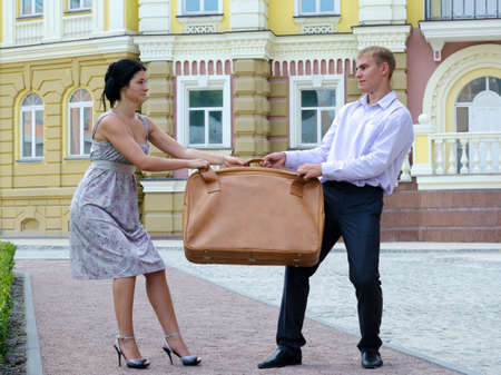 Stylish young couple fighting over luggage and playing tug of war with a large suitcase on an urban street Archivio Fotografico