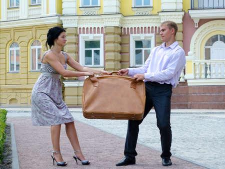 combattimenti: Elegante giovane coppia in lotta per i bagagli e la riproduzione di tiro alla fune con una valigia di grandi dimensioni su una strada urbana