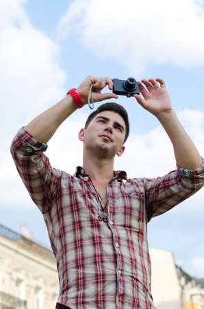 facing to camera: Low angle view of a young man taking a photograph with a compact camera against a cloudy blue sky