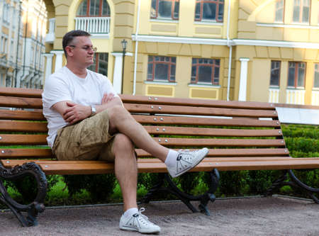 Casual middle-aged man sitting waiting on a wooden bench in an urban environment photo