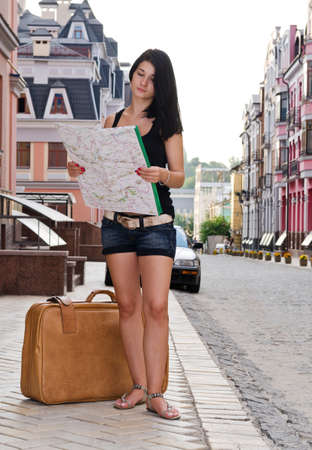 Woman tourist standing in a street in a foreign town with her luggage and map which she is reading to find directions