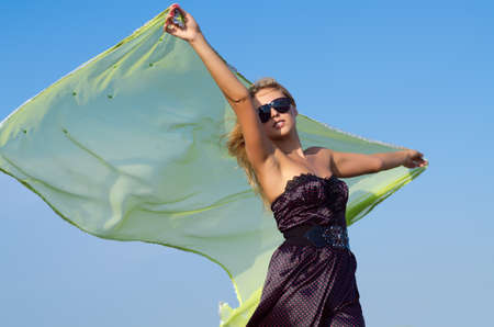 flutter: Beautiful woman in a stylish dress and sunglasses holding up a green scarf to flutter behind her in the breeze Stock Photo