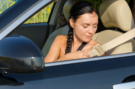 commencing: Woman sitting in a car reaching behind her to put on her seatbelt before commencing her journey