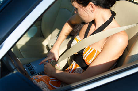 14803625: Woman driver leaning down to tighten her safety belt before driving away Stock Photo