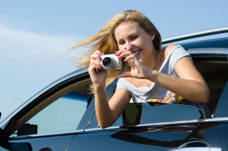 Laughing woman taking digital photographs leaning out of the rear passenger window of a motor car