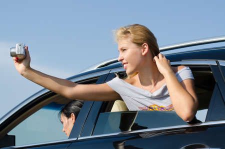 arm extended: Young blonde woman leaning out of the passenger window taking photos from a car Stock Photo