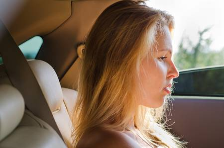 Profile of an attractve dejected blonde woman sitting in a car Stock Photo - 14826322